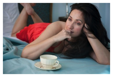 Woman lying on bed with cup of coffee